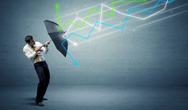 Business person with umbrella and stock market arrows concept Stock Photos