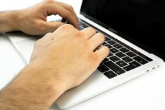 Business person using the keyboard of a laptop on a white table. Person working royalty free stock photos