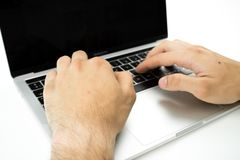 Business person using the keyboard of a laptop on a white table. Person working stock photography