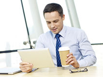 Business person using tablet in office. Caucasian businessman looking at tablet computer holding coffee cup smiling in office Royalty Free Stock Photo