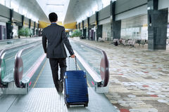 Business person walk toward escalator Stock Photos
