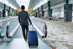Business person walk toward escalator Stock Photos