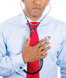 Business person, worker listening to his heart with stethoscope. Self-diagnosis Royalty Free Stock Images