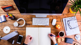 Business person working at office desk holding a notebook. Business person working at office desk, writing into a notebook. Smart phone on the table. Copy space Royalty Free Stock Photos