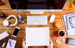 Business person working at office desk holding paper sheet. Business person working at office desk. Holding a sheet of paper. Smart phone on the table. Copy Stock Photos