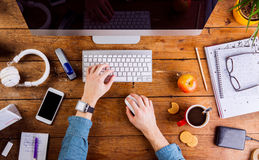 Business person working at office desk wearing smart watch. Business person working at office desk. Smart watch on hand and smart phone on the table. Coffee cup Stock Image