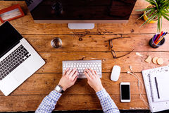 Business person working at office desk wearing smart watch. Business person working at office desk, writing on computer keyboard. Smart watch on hand and smart Stock Photo