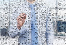A business person is writing a numerous business icons on the glass screen Stock Photography