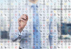 A business person is writing a numerous business and social media icons on the glass screen. Stock Photos