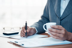 Business person writing report in office Royalty Free Stock Photo