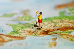 Business Or Personal Travel Concept. Two miniature figurines of a man carrying luggage and his wife embracing while standing on a map of Europe Royalty Free Stock Photography