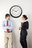 Business persons. Male and female businesspersons under clock. Vertically framed shot Royalty Free Stock Photos