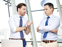 Business persons chatting in office. Two caucasian business persons standing and chatting in office Royalty Free Stock Images
