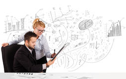 Business persons at desk with hand drawn charts Stock Photo