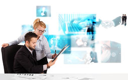 Business persons at desk with modern tech images at background Stock Photo