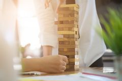 Business persons planning a project brown wood building block to Royalty Free Stock Photo