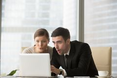 Business persons puzzled of breaking news online. Businessman and businesswoman feeling surprised when sitting at office desk and looking on laptop screen Royalty Free Stock Photos