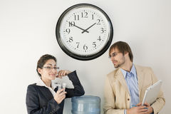 Business persons at Water Cooler. Male and female businesspersons talking under clock. Horizontally framed shot Royalty Free Stock Photography
