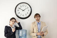 Business persons at Water Cooler. Male and female businesspersons talking under clock. Horizontally framed shot Royalty Free Stock Photos