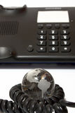 Business phone and glass globe Royalty Free Stock Photography