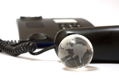 Business phone and glass globe Stock Photography