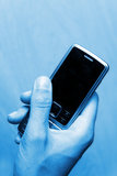 Business phone mobile. In female hand, blue colored bakground Royalty Free Stock Photos