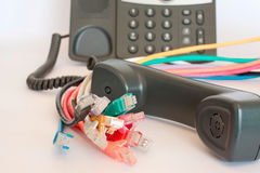 Business phone and networking. VOIP telephone handset with multiple different colored ethernet cables Stock Photos