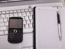 Business. Phone and notepad on laptop. Stock Photos