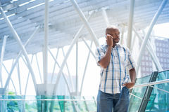 Business phonecall. Businessman in casual making a serious phonecall inside Stock Image