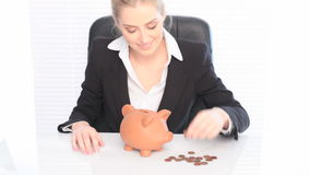 Business Piggy Bank Savings. A smiling businesswoman sits at her desk placing coins in a piggy bank, savings concept stock footage