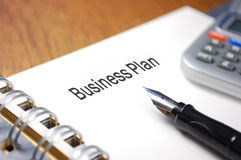 Business plan. Report entitled Business Plan with a fountain pen and calculator Stock Photography