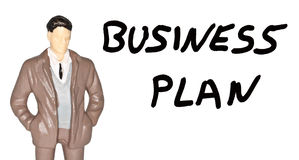 Business Plan. Business figurine man and a business plan written in words Stock Images