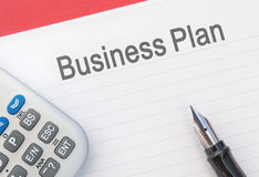 Business plan. Report entitled Business Plan with a fountain pen and calculator Royalty Free Stock Images