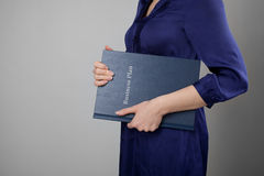 Business plan. Woman holding business plan. Gray background Royalty Free Stock Photography