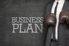 Business plan on blackboard with businessman Stock Photography