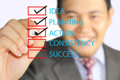 Business plan checklist. Young businessman marks checking list of his business plan steps Royalty Free Stock Photos