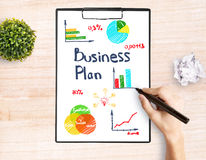 Business plan concept. Hand drawing creative sketch on clipboard placed on wooden desktop with plant. Business plan concept Stock Images