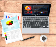 Business plan concept. Top view of a couple of paper sheets of a business plan, a pen, a cup of coffee, a computer notebook with a financial app, wooden Royalty Free Stock Image