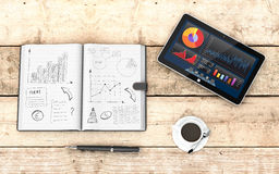 Business plan concept. Top view of paper notebook with hand drawn doodles of a business plan, a pen, a cup of coffee, a tablet pc with a financial app, wooden Royalty Free Stock Photo