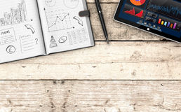 Business plan concept. Top view of paper notebook with hand drawn doodles of a business plan, a pen, a tablet pc with a financial app, wooden background with Stock Images