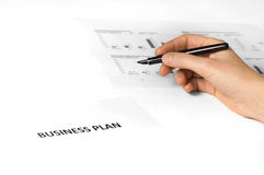 Business plan with hand + pen. Paper on desk with business plan on it. hand holding pen. paper with graphics on the background Stock Image