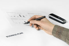 Business plan with hand + pen. Paper on desk with business plan on it. hand holding pen. paper with graphics on the background. cellphone on background Royalty Free Stock Photos