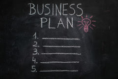 Business plan list and lightbulb on black chalkboard Royalty Free Stock Photography