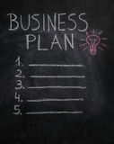 Business plan list and lightbulb on black chalkboard Royalty Free Stock Photos