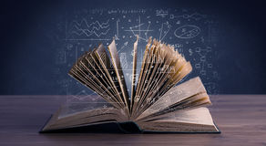 Business plan over book. Hand-drawn financial plans and charts coming out of an open book Stock Photos