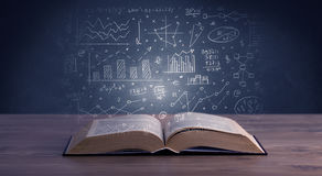 Business plan over book. Hand-drawn financial plans and charts coming out of an open book Royalty Free Stock Photo