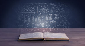 Business plan over book. Hand-drawn financial plans and charts coming out of an open book Royalty Free Stock Photos