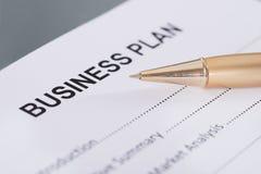 Business plan and pen. Business plan and golden pen. Closeup shot stock photography