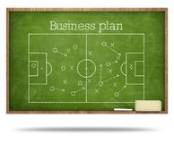 Business plan text and soccer fied on blackboard royalty free stock photography