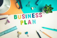 Business plan word on desk office background with supplies. Stock Photo